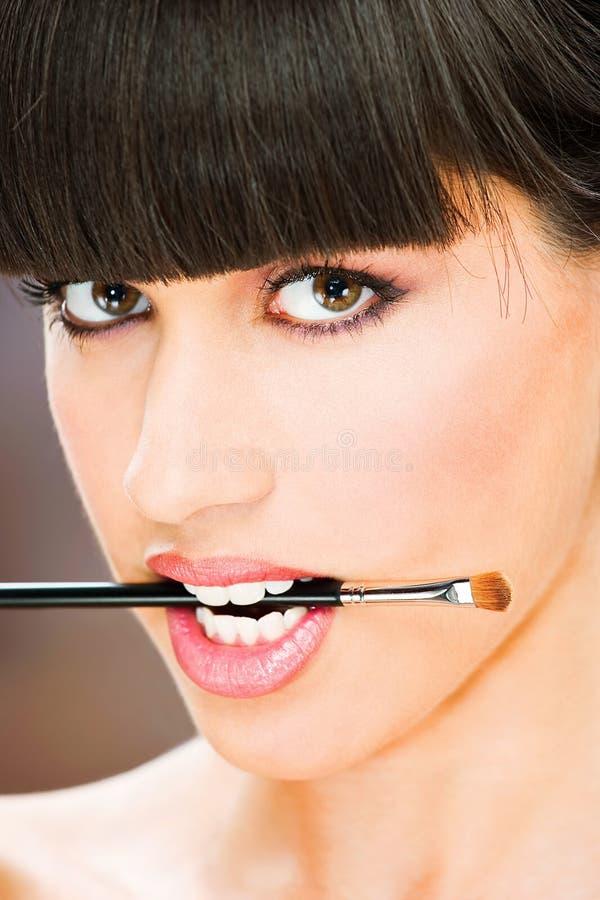 Kobieta chwyt uzupełniał muśnięcie między zębami zdjęcia royalty free