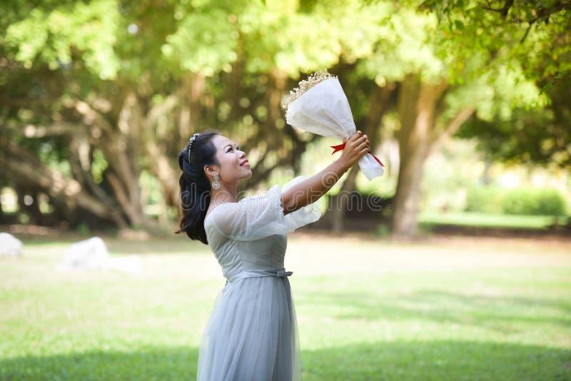 Kobieta chwyta bukieta kwiat Daje kwiaty obrazy royalty free