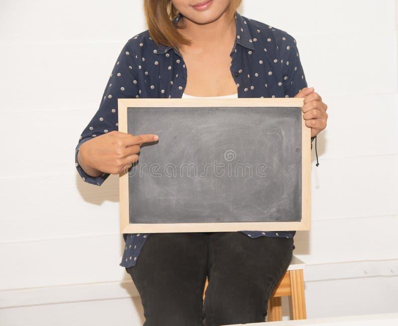 Kobieta chwyta chalkboard zdjęcia royalty free