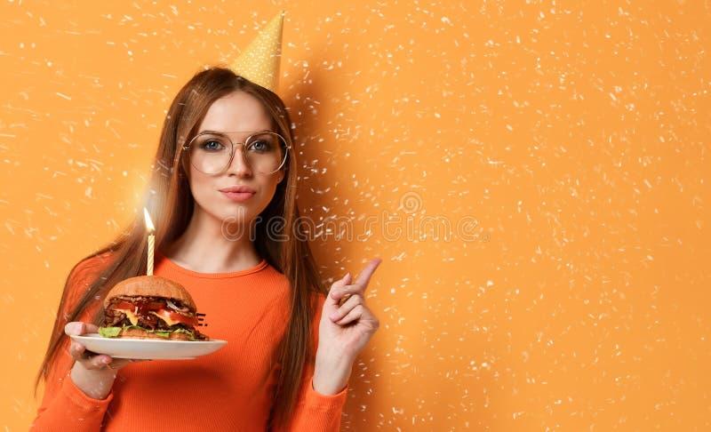 Kobieta chwyta wołowiny cheeseburger duża marmurowa kanapka dla przyjęcia urodzinowego z płonącą świeczką na pastelowym żółtym tl zdjęcie stock