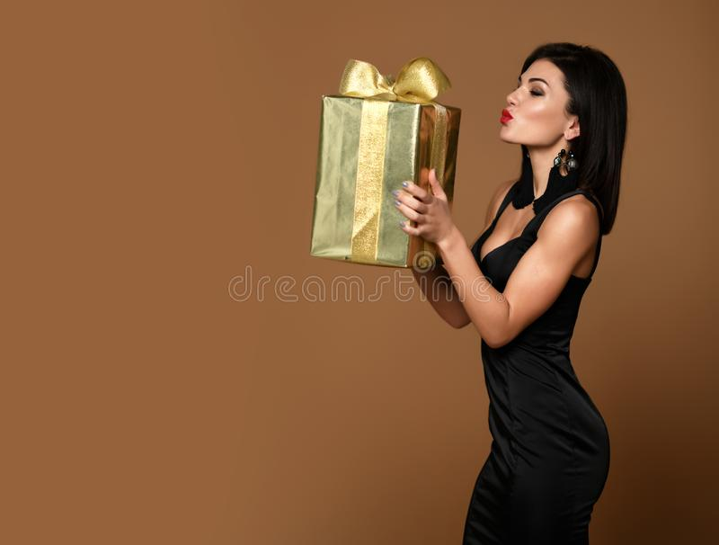 Kobieta chwyta złocisty zakupy przedstawia prezenta pudełko dla szczęśliwego valentines dnia, urodziny na beżu lub obrazy stock