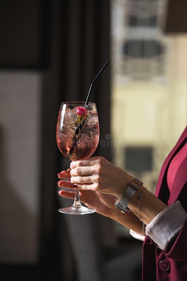 Kobieta chwyty relaksuje alkoholiczka różowego koktajl z różą na wierzchołku obraz royalty free