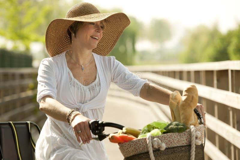 Kobieta cicyling z warzywami w jej koszu zdjęcie royalty free
