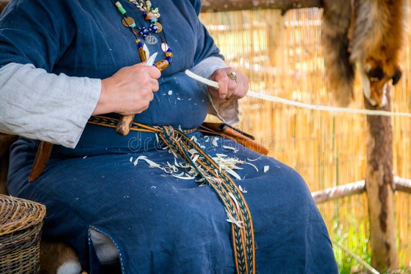 Kobieta cieśla jest ubranym wiejską odzież i cyzelowanie drewniany sti obrazy stock