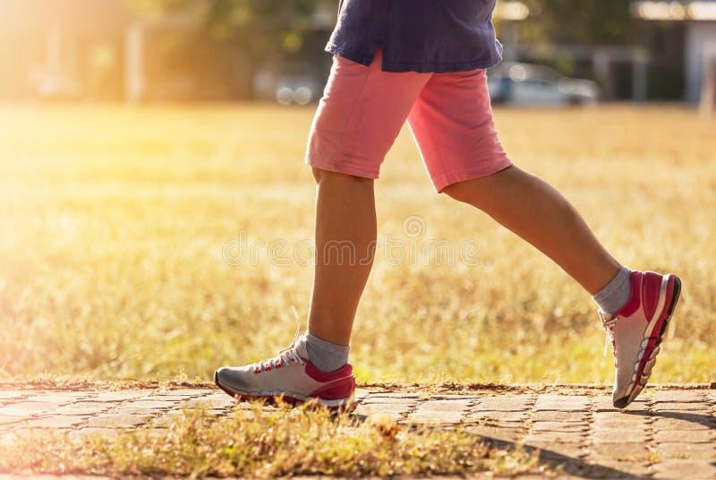 Kobieta cieki jogging na drodze w zmierzchu obraz stock