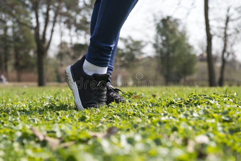 Kobieta cieki w czarnych sneakers na trawie na gazonie na słonecznym dniu, bawją się buty obrazy stock