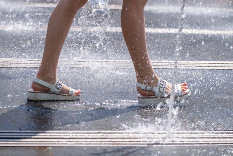 Kobieta cieki w sandałach pośród odświeżającej kiści miasto fontanna na gorącym letnim dniu fotografia stock