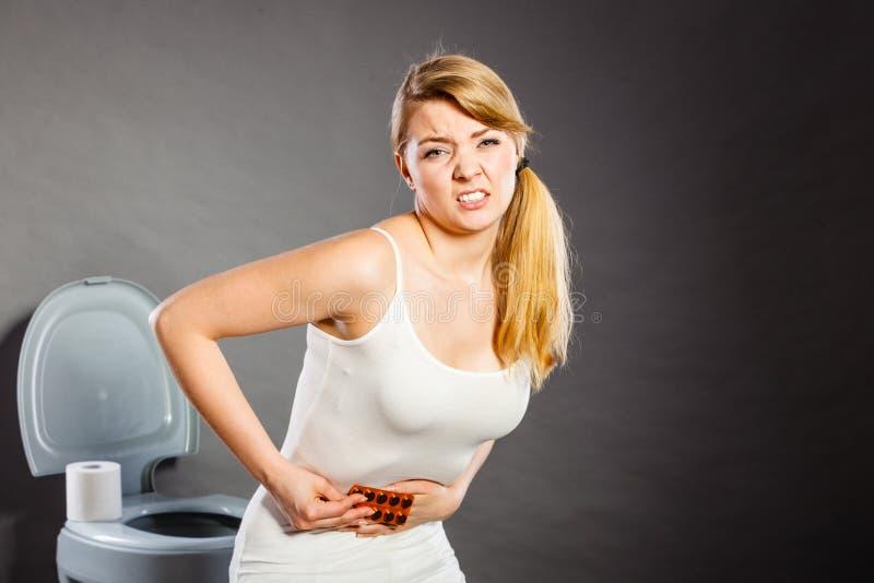 Kobieta cierpi od brzucha bólu chwytów pigułek w toalecie obrazy royalty free