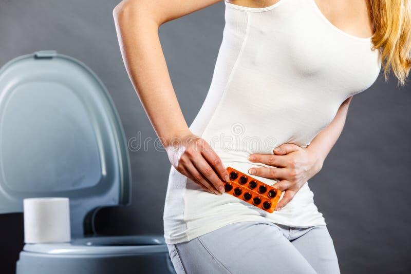Kobieta cierpi od brzucha b?lu chwyt?w pigu?ek w toalecie zdjęcie stock