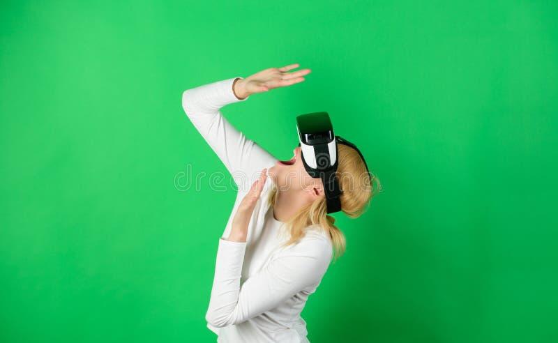 Kobieta cieszy się cyber zabawy doświadczenie w vr Zadziwiająca młoda kobieta dotyka powietrze podczas VR doświadczenia zabawna k fotografia stock