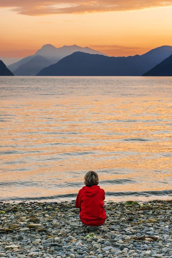 Kobieta cieszy się pięknego zmierzchu krajobraz na fjord obraz royalty free