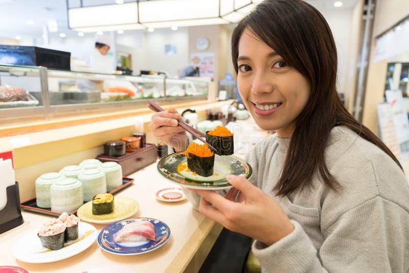 Kobieta cieszy się suszi przy japońską restauracją obrazy stock