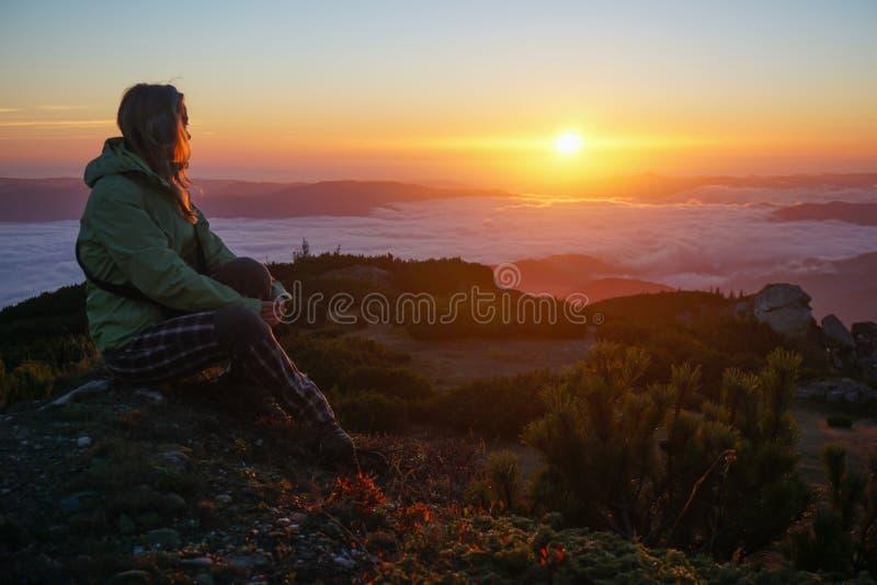 Kobieta cieszy się wschód słońca w górach