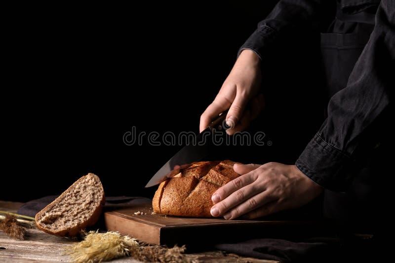 Kobieta ciie świeżego chleb na stole przeciw ciemnemu tłu zdjęcia stock
