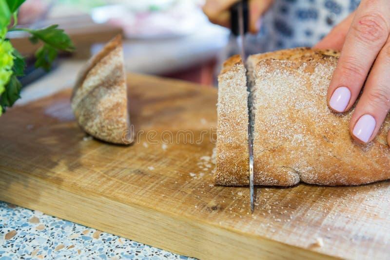 Kobieta ciie świeżego domowej roboty chleb na drewnianej desce obrazy royalty free