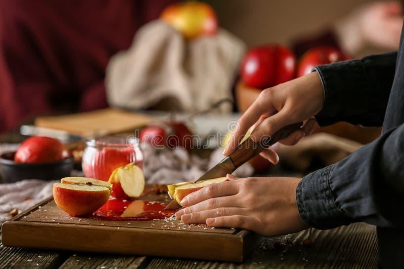 Kobieta ciie świeżego jabłka przy drewnianym stołem zdjęcia stock