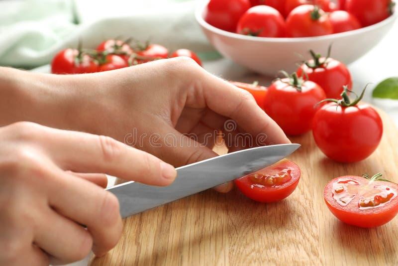 Kobieta ciie świeżych czereśniowych pomidory na pokładzie, zbliżenie zdjęcie stock