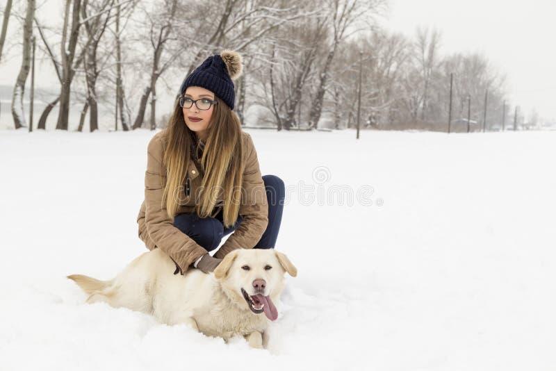 Kobieta cuddling jej psa w śniegu fotografia royalty free