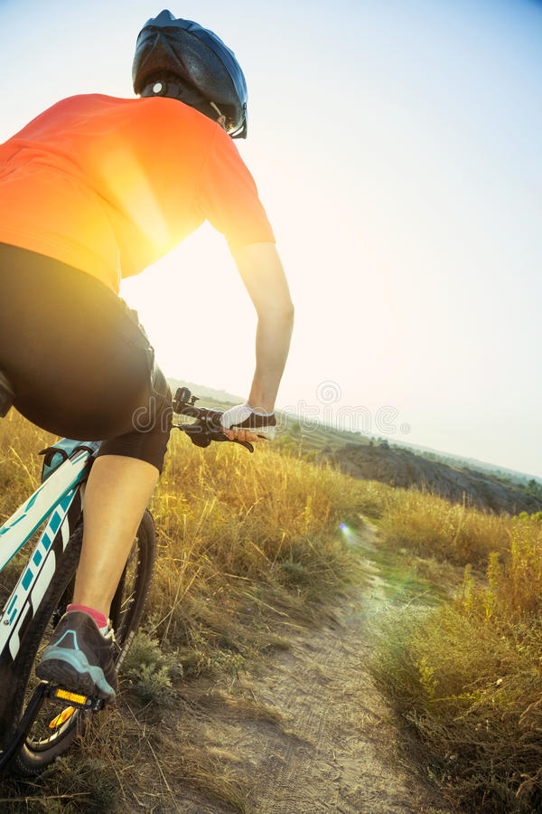Kobieta cyklista z świeceniem od położenia słońca obrazy stock