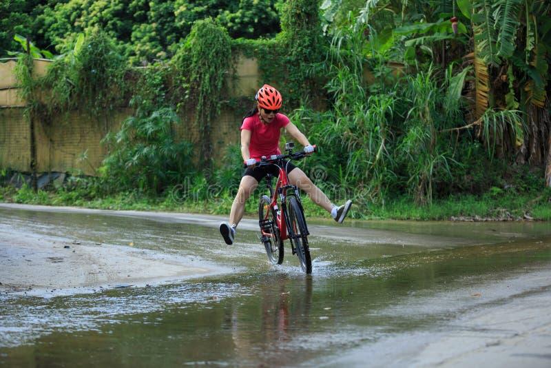 Kobieta cyklisty kolarstwa rower górski biegał w wodzie na śladzie fotografia royalty free