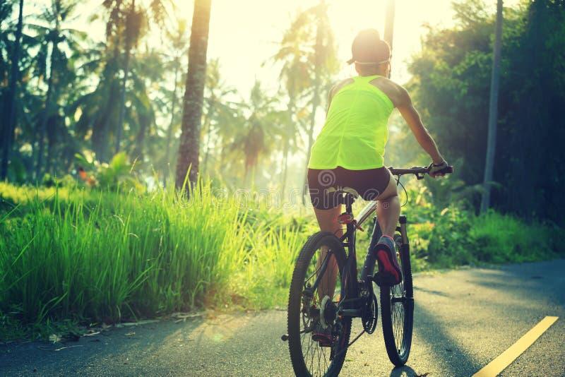 Kobieta cyklisty kolarstwo na tropikalnym lasowym śladzie obrazy stock