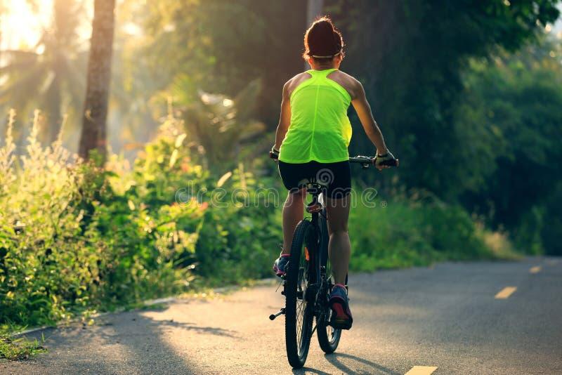 Kobieta cyklisty kolarstwo na tropikalnym lasowym śladzie obraz stock