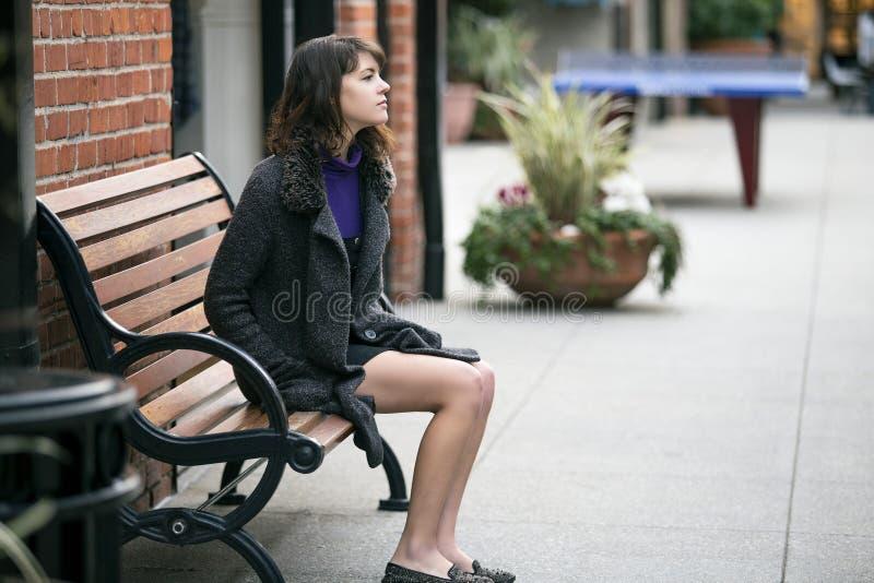 Kobieta Czekać na pociąg lub autobus Podczas gdy Siedzący na ławce obraz stock