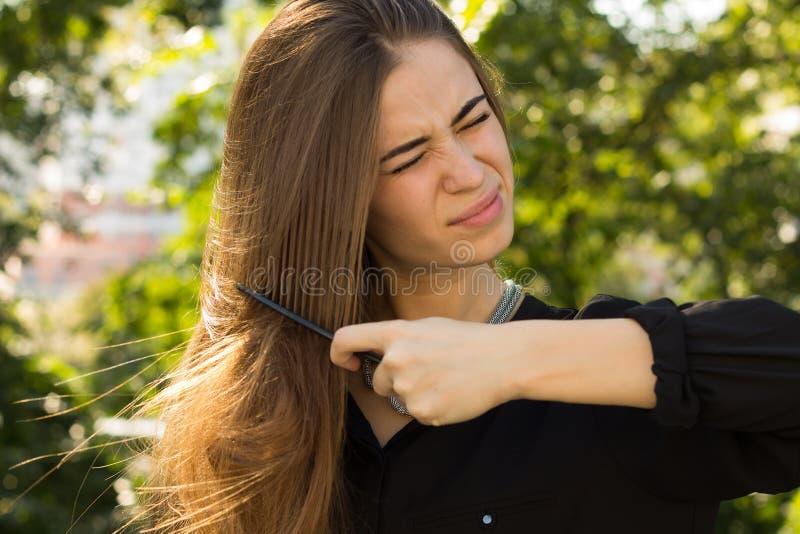 Kobieta czesze jej włosy w parku fotografia stock