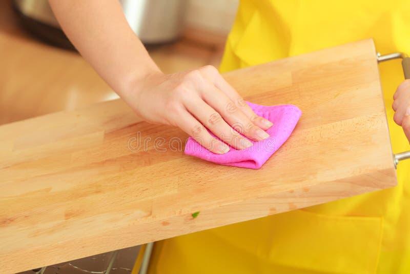 Kobieta czyści drewnianą tnącą deskę z łachmanem zdjęcie royalty free