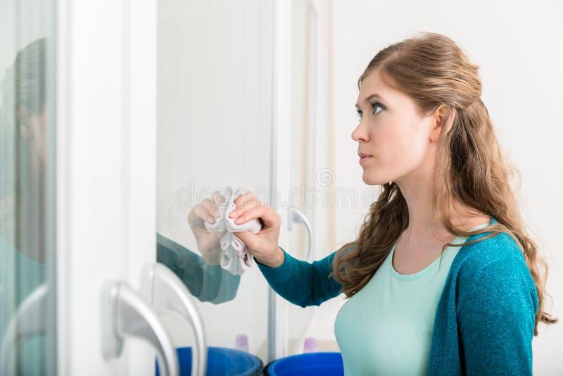 Kobieta czyści drzwiowego szkło z płótnem fotografia royalty free