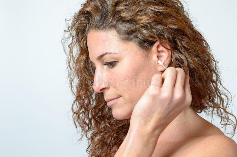 Kobieta czyści jej ucho z bawełnianym mopem fotografia stock