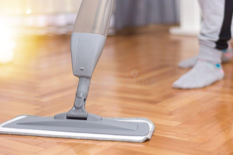 Kobieta czyści parkietowej podłogi myje kwacz w domu fotografia royalty free