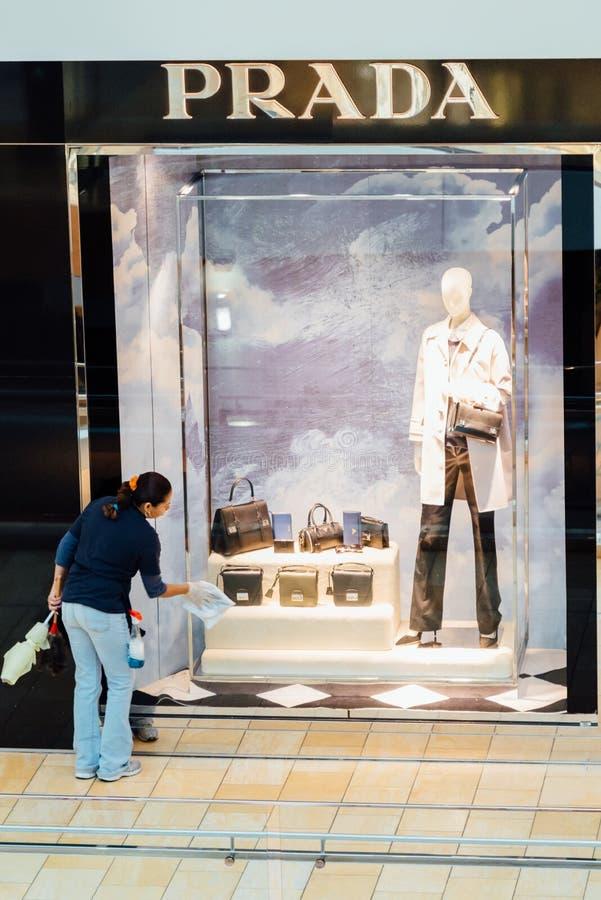 Kobieta czyści PRADA sklepowego okno przy zakupy centrum handlowym zdjęcia stock