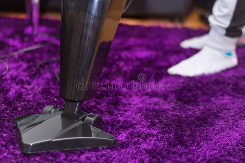 Kobieta czyści purpurowego dywan z nowożytny próżniowy czystym w żywym pokoju obraz stock