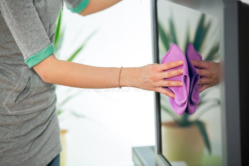Kobieta czyści TV z cleanser w domu obraz royalty free