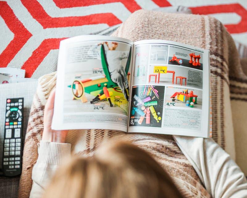 Kobieta czyta IKEA katalogu meblowania dom żartuje meble fotografia royalty free
