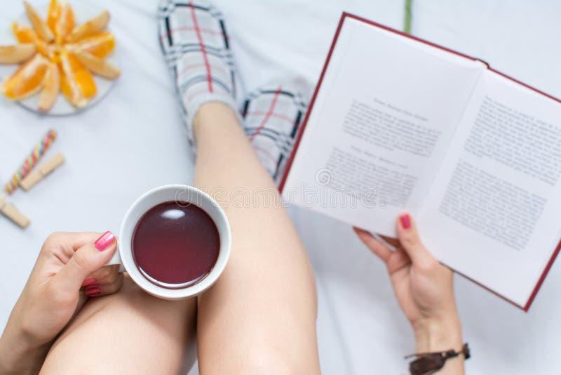 Kobieta czyta książkę i ma filiżankę herbata fotografia stock