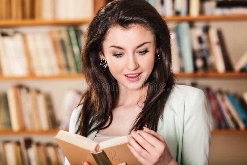 Kobieta czyta książkę przed półka na książki obraz stock