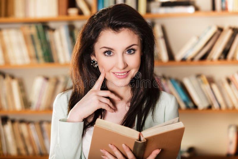 Kobieta czyta książkę przed półka na książki zdjęcia royalty free