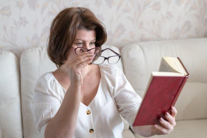 Kobieta czyta książkę przez dwa szkieł z nadwyrężonym wzrokiem obraz royalty free
