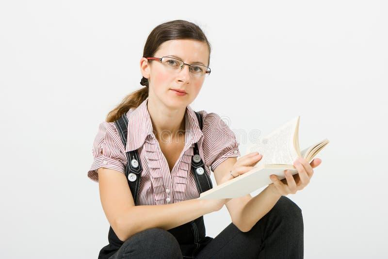 Kobieta czyta książkę w szkłach zdjęcie royalty free