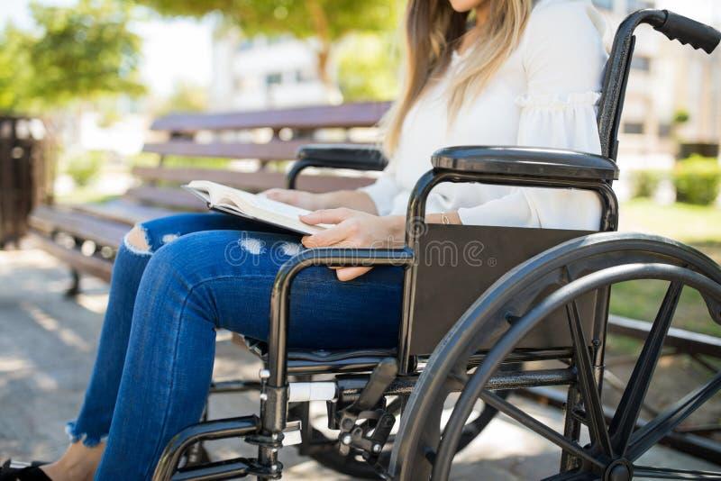 Kobieta czyta książkę w wózku inwalidzkim fotografia stock