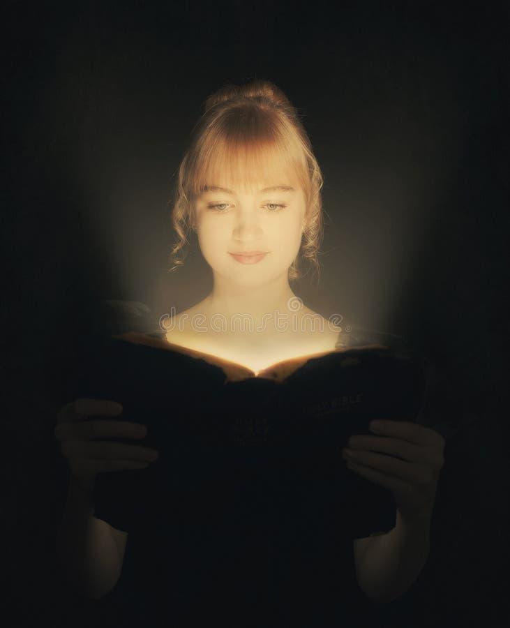 Kobieta czyta rozjarzoną biblię. zdjęcie stock