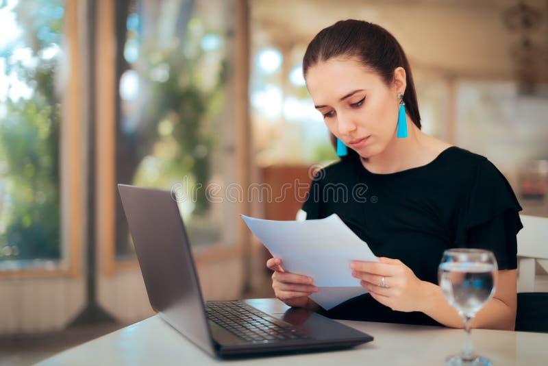 Kobieta Czyta Znacząco dokument podczas gdy Pisać na maszynie na laptopie zdjęcie stock