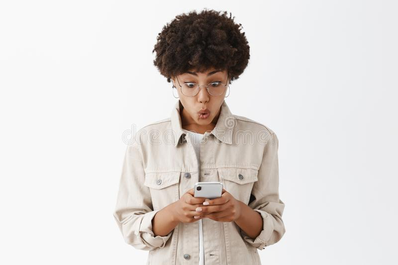 Kobieta czytaj?ca o zadziwiaj?cej ofercie w internecie, czu? ekscytuj?, chce i?? czek za Imponuj? ciekawi? ?licznego afrykanina fotografia royalty free