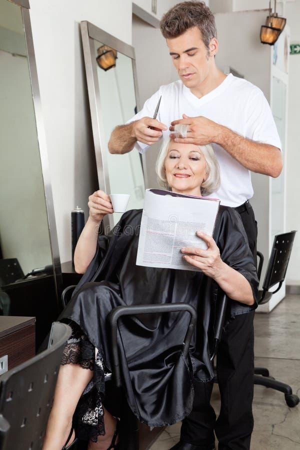 Kobieta Czytelniczy magazyn Podczas gdy Mieć ostrzyżenie obraz stock