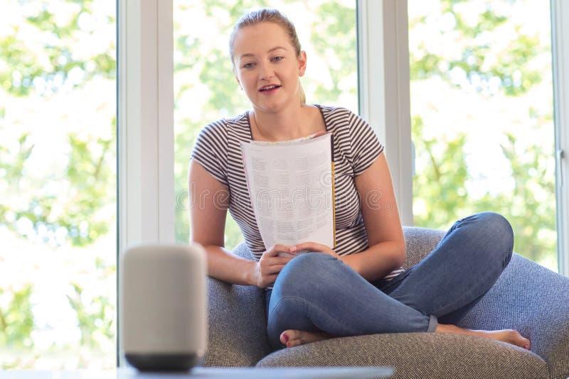 Kobieta Czytelniczy magazyn Pyta Cyfrowemu Pomocniczego pytanie W Domu zdjęcia stock