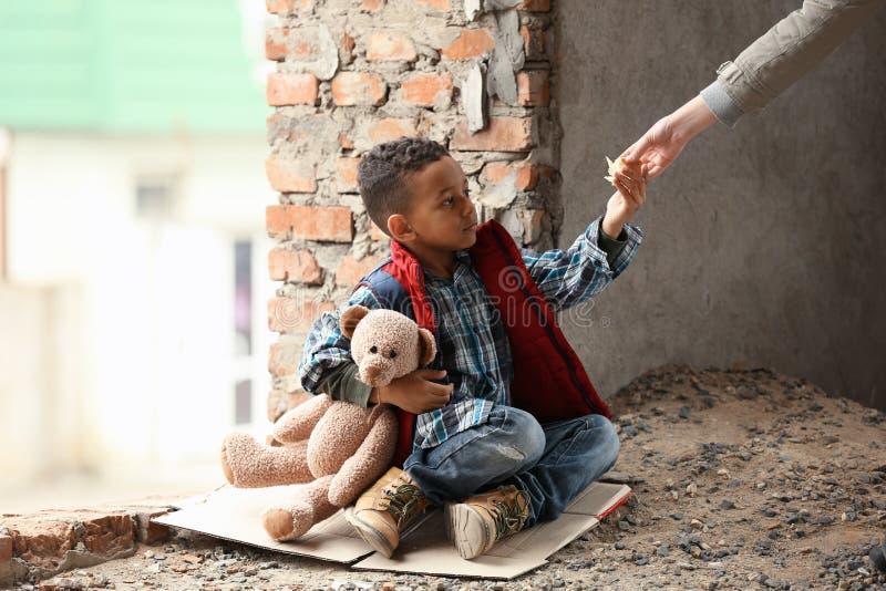 Kobieta daje kawałkowi chleb śliczna chłopiec w zaniechanym budynku obrazy royalty free