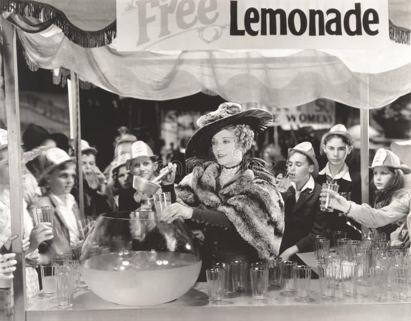 Kobieta daje out swobodnie lemoniadzie dzieci przy jarmarkiem obrazy stock