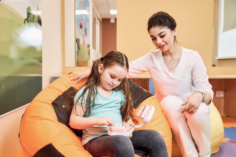Kobieta dentysta uczy małej dziewczynki szczotkować jej zęby fotografia stock